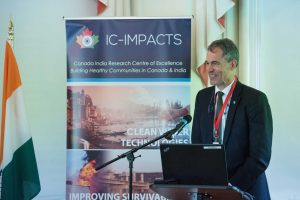 Bill Barrable, CEO of the Rick Hansen Institute, at the podium in front of an audience at IC-IMPACTS Gateway to India, Innovation, and Economic Development