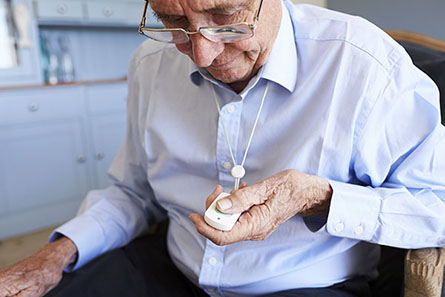 elderly man with a medical alert button from Presidium Health's STAT platform