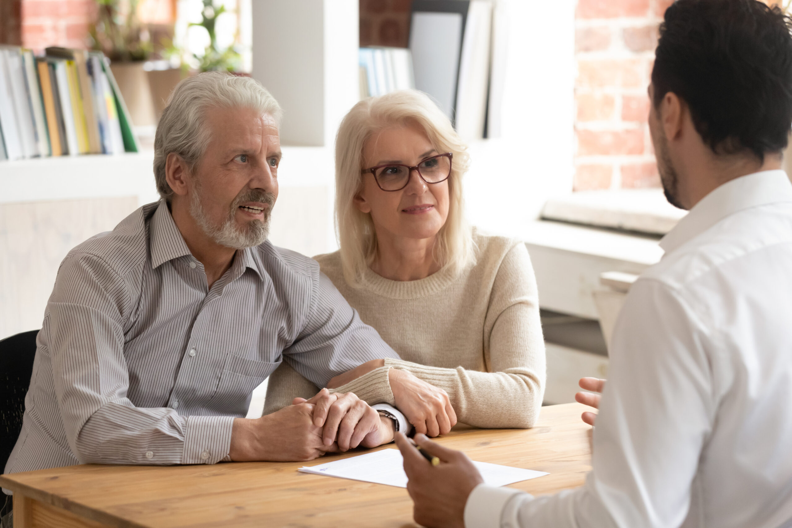 Happy mature couple meeting with male real estate agent or broker discuss future property purchase contract terms, excited pensioner husband and wife talk with financial consultant taking loan