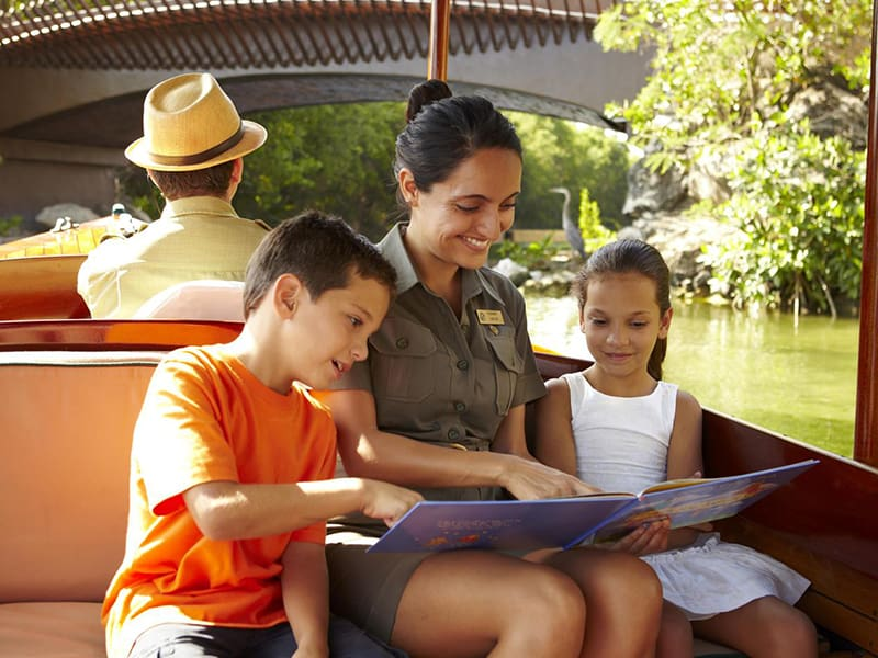 2 kids reading with Fairmont Mayakoba Riviera Maya guide on a boat