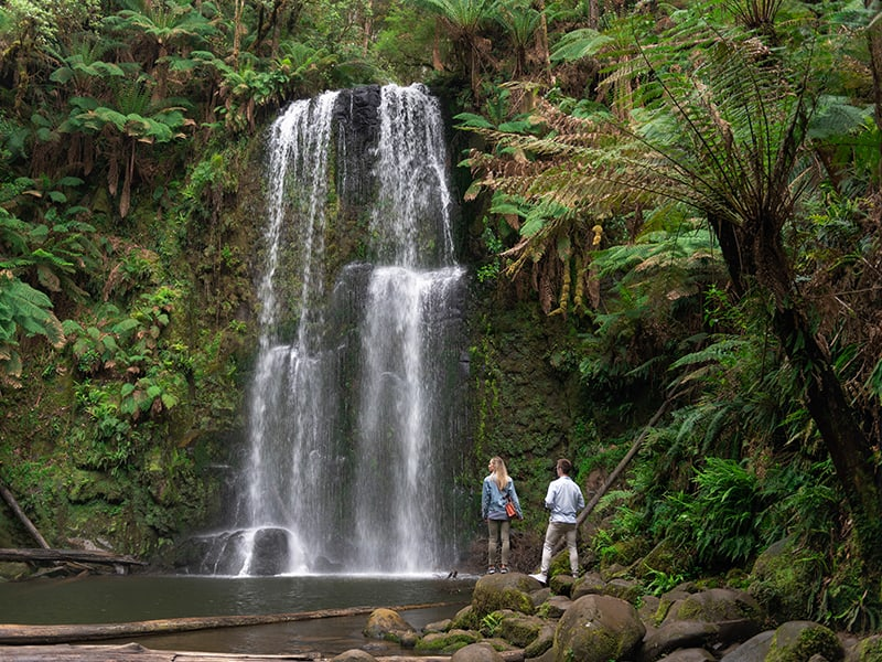 Two people stand at the base of waterfall in Victoria, Australia
