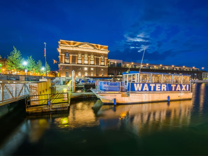 A water taxi along the Fells Point Waterfront at night, in Baltimore, Maryland.