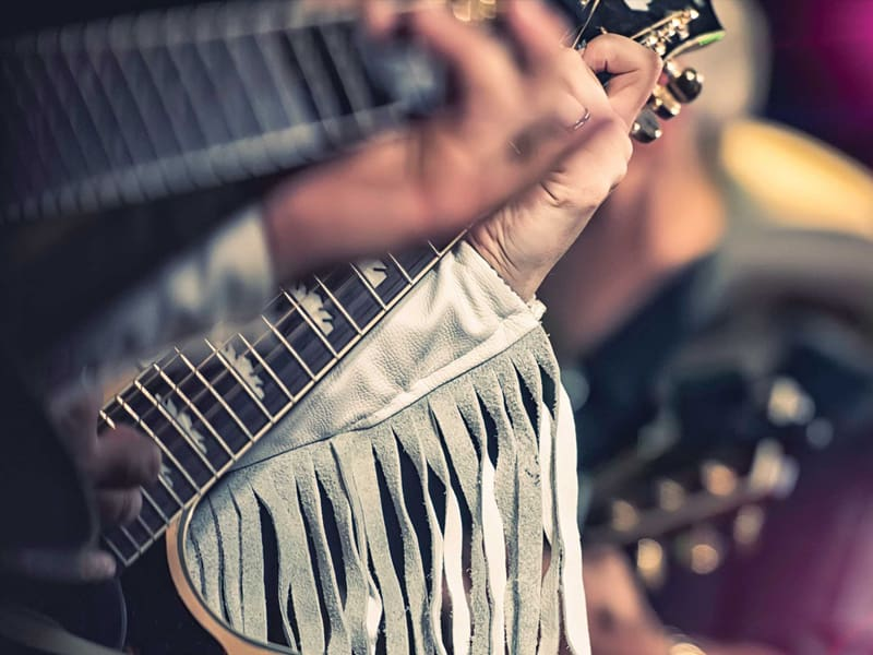Closeup photo of 2 peoples hands playing guitar with fringe leather jacket