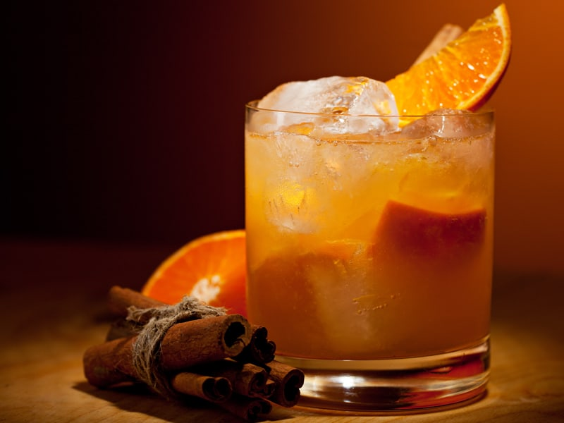 Cocktail in a glass with orange slices and cinnamon sticks