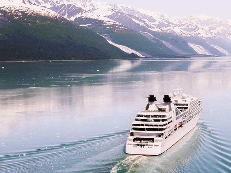Seabourn ship sailing by snowy mountains in Alaska