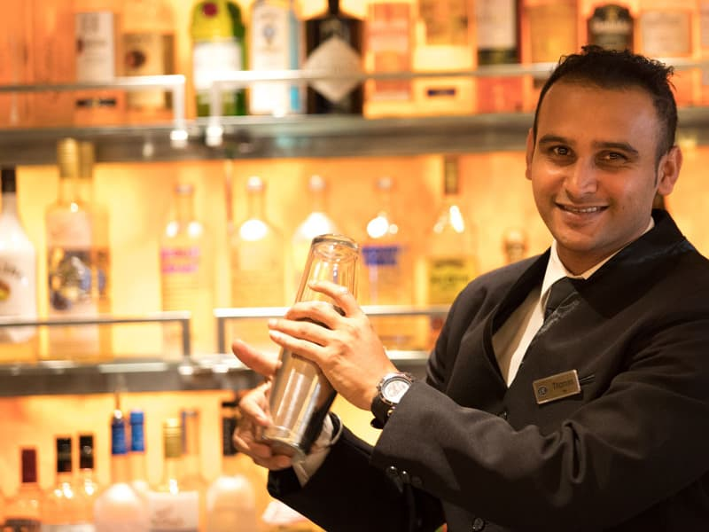 Regent Seven Seas male bartender shaking up a drink