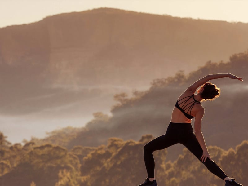 Woman in fitness clothes stretching with mountain and trees in background