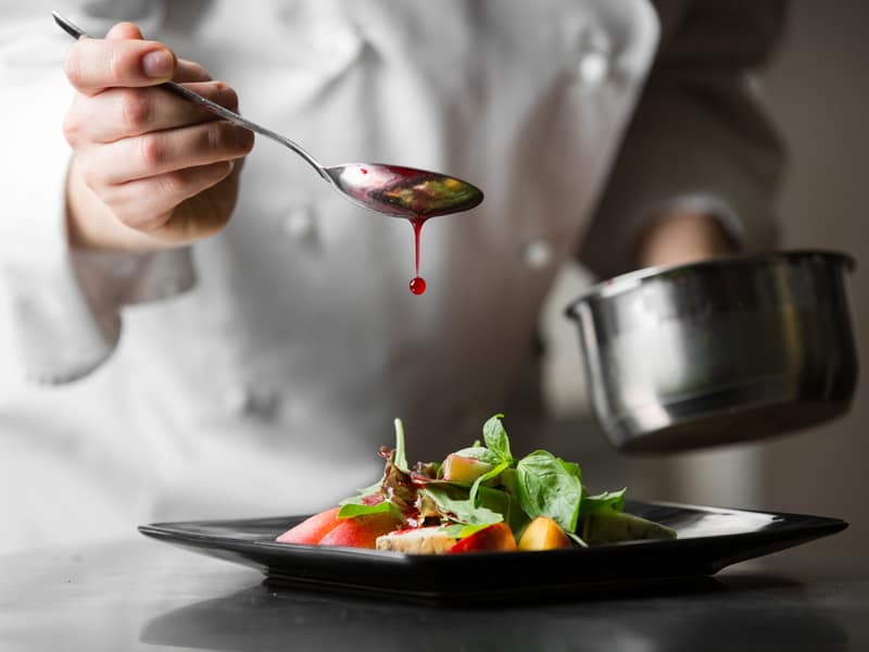 Chef drizzling berry vinaigrette over plate of fruit, vegetables, and cheese