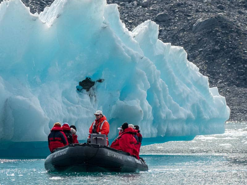 Expedition raft in Greenland next to icebergs with 7 passengers in red coats