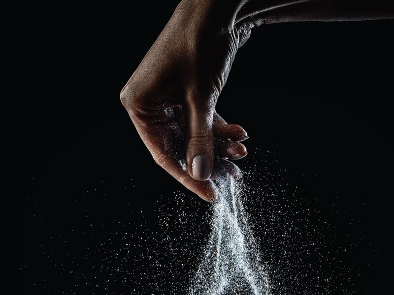Closeup of hand sprinkling a large amount of salt