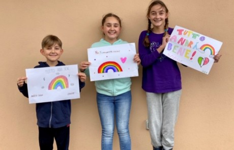 Children in Italy holding their rainbow artwork.