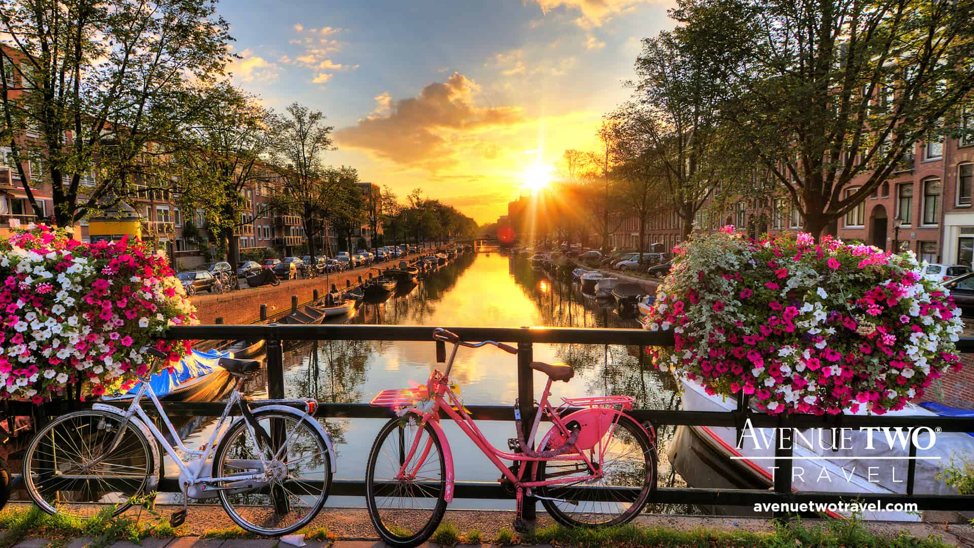 A2T background image of sunrise over Amsterdam, The Netherlands, with flowers and bicycles on the bridge in spring