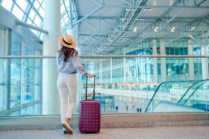 Young woman in hat with baggage in international airport. Airline passenger in an airport lounge waiting for flight aircraft