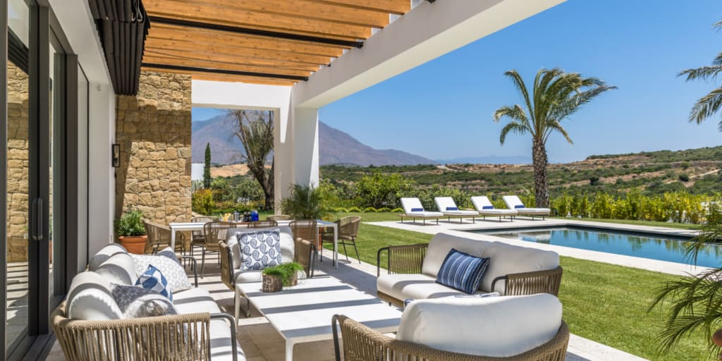 Villa at Finca Cortesin in Andalucia, porch lounge view of pool and landscape with mountains and palm tree