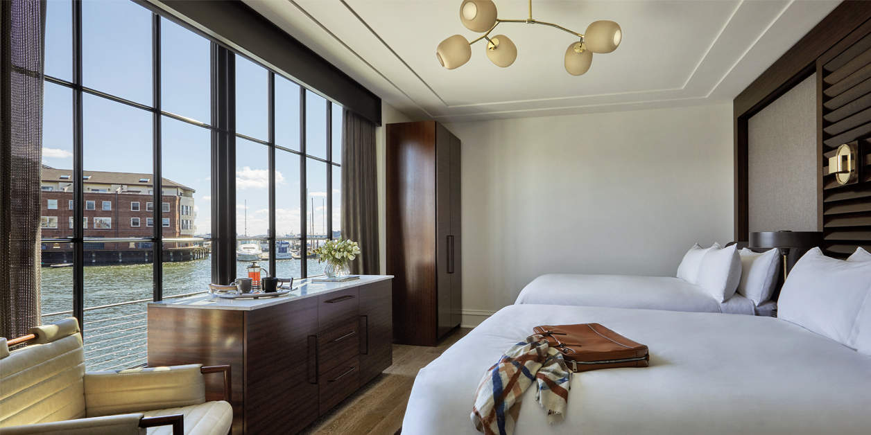 Sagamore Pendry interior room with bed and large windows overlooking the harbor