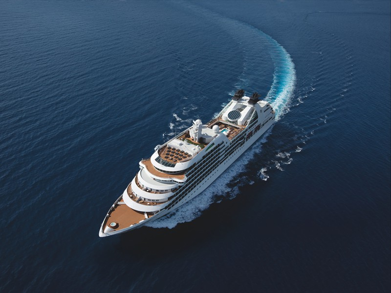 Aerial view of a Seabourn ship out to sea, turning in the water.