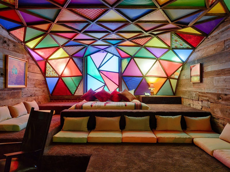 21c hotel Louisville cyclone artist suite, bed and pillows with large colorful stained glass windows