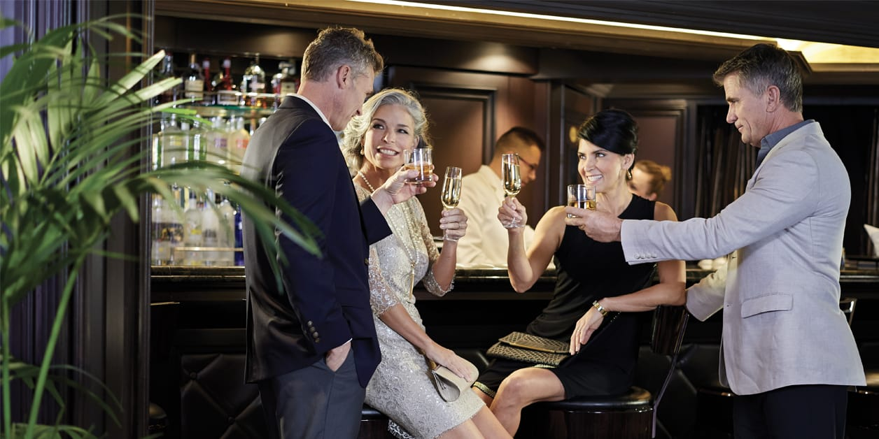 two couples enjoying cocktails at the bar, toasting, on an Oceania Cruise