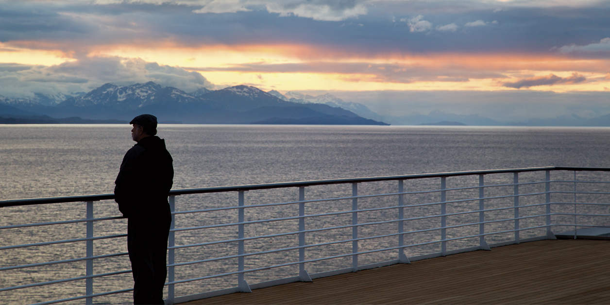 Man standing on deck of Oceania ship watching sunset by the railing.