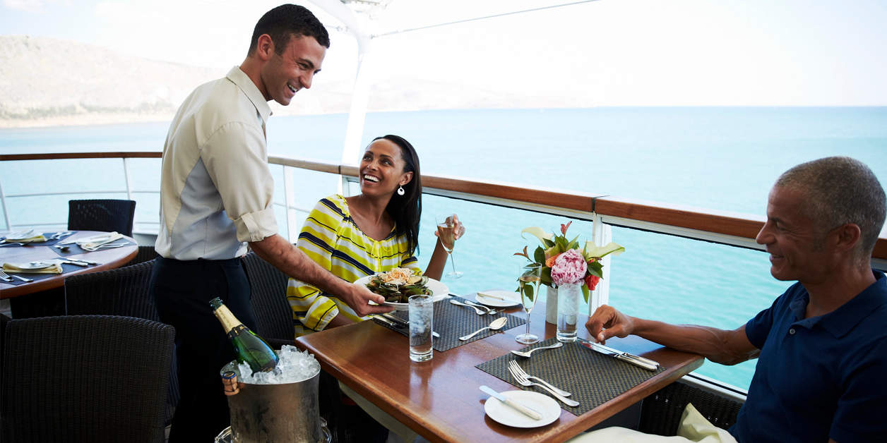 Server and couple laughing and talking as server gives couple food. On the deck of Seabourn ship looking out over ocean.