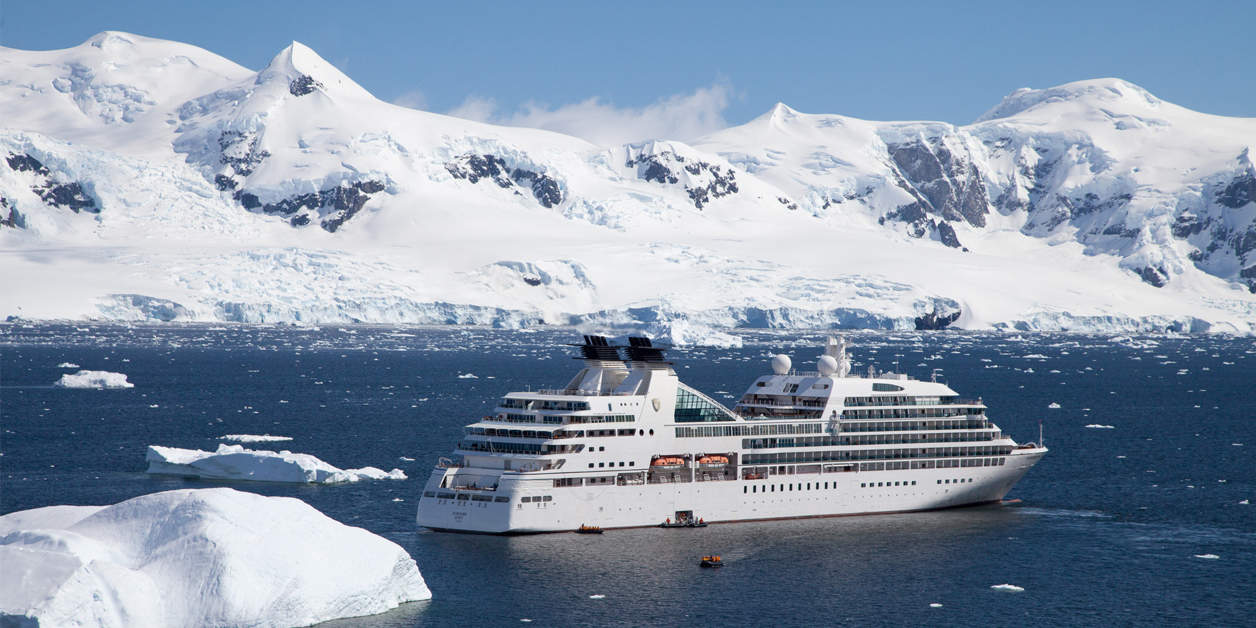 Seabourn Quest sailing past snowy mountains