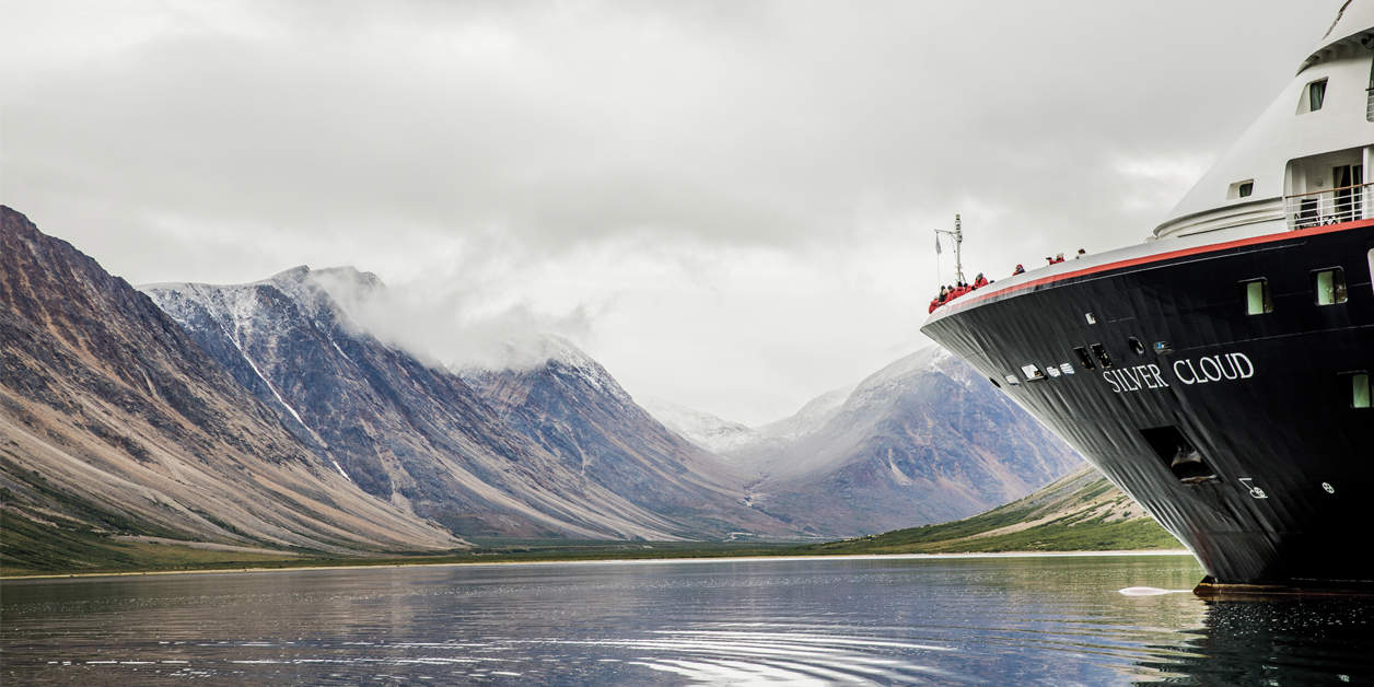 Silversea Silver Cloud sailing through a fjord with mountains in the Arctic