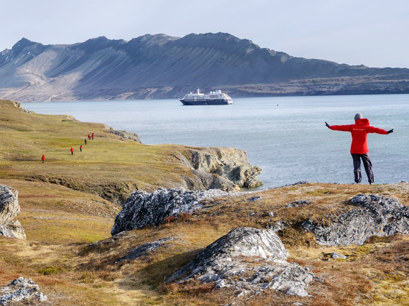 Silversea guests in red jackets on an expedition adventure in the Arctic. One guest in foreground with arms spread out enjoying the moment.