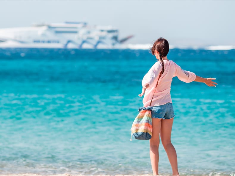 This photo shows a woman standing with her arms spread open on a tropical beach with large cruise liners in the distance.