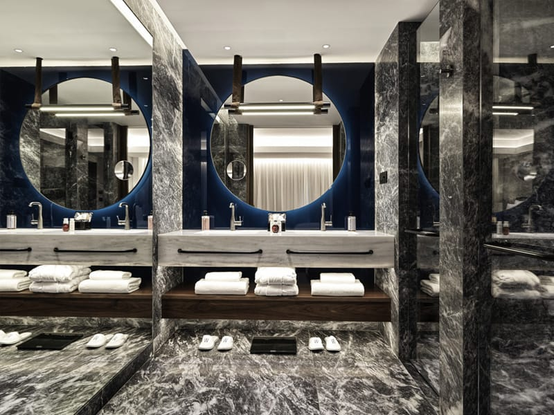 Bathroom view at Athens Capital Center Hotel - MGallery Collection with marble surfaces and circular mirror