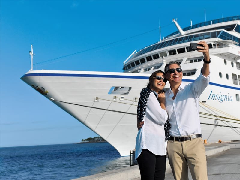 Man and woman couple taking a selfie on a dock infront of the Oceania Insignia ship.