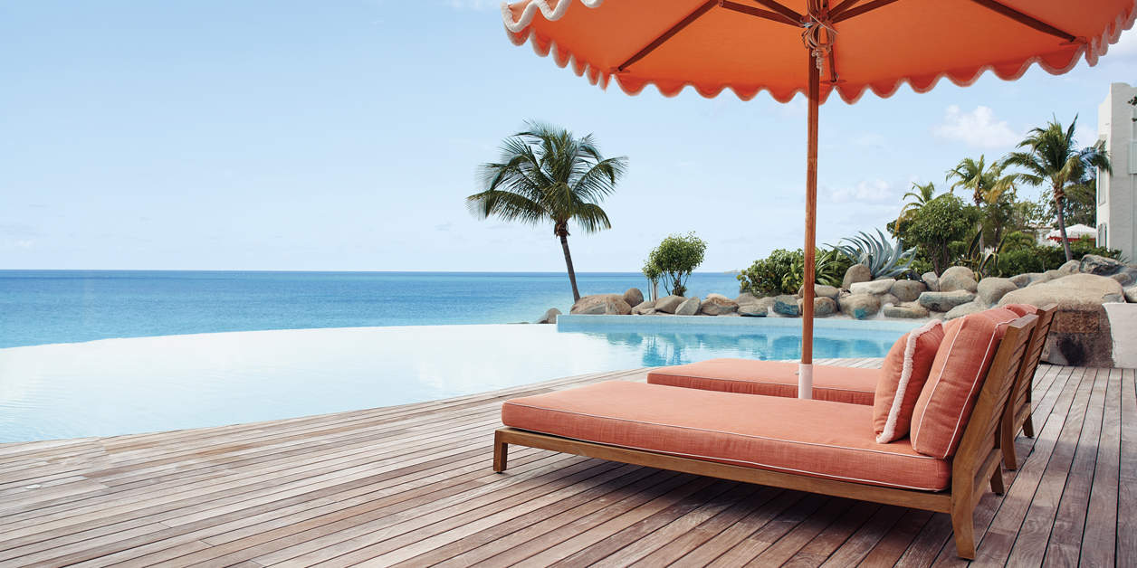 Belmond La Samanna lounge chairs by the infinity pool, facing ocean