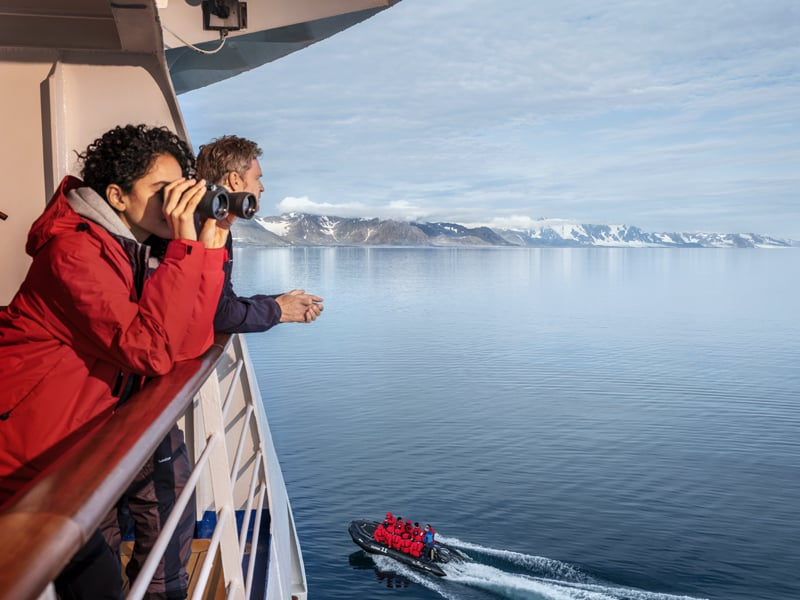 Silversea photo of expedition boat in background and 2 guest looking off side of ship in foreground, one looking through binoculars