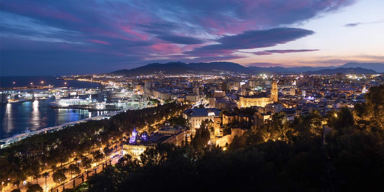 An aerial long exposure photograph of the city of Malaga, Spain during a beautiful sunset.