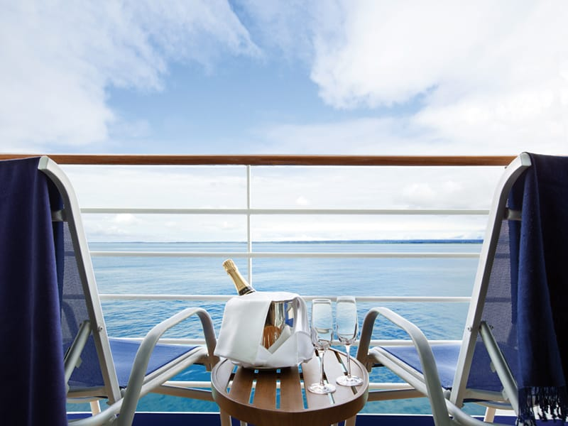 View off the veranda of Oceania Cruise with champagne bottle in ice bucket and 2 empty patio chairs.