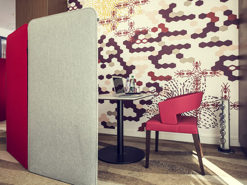 Workspace area with red chair, laptop and colorful wallpaper at Mercure Paris Montmartre