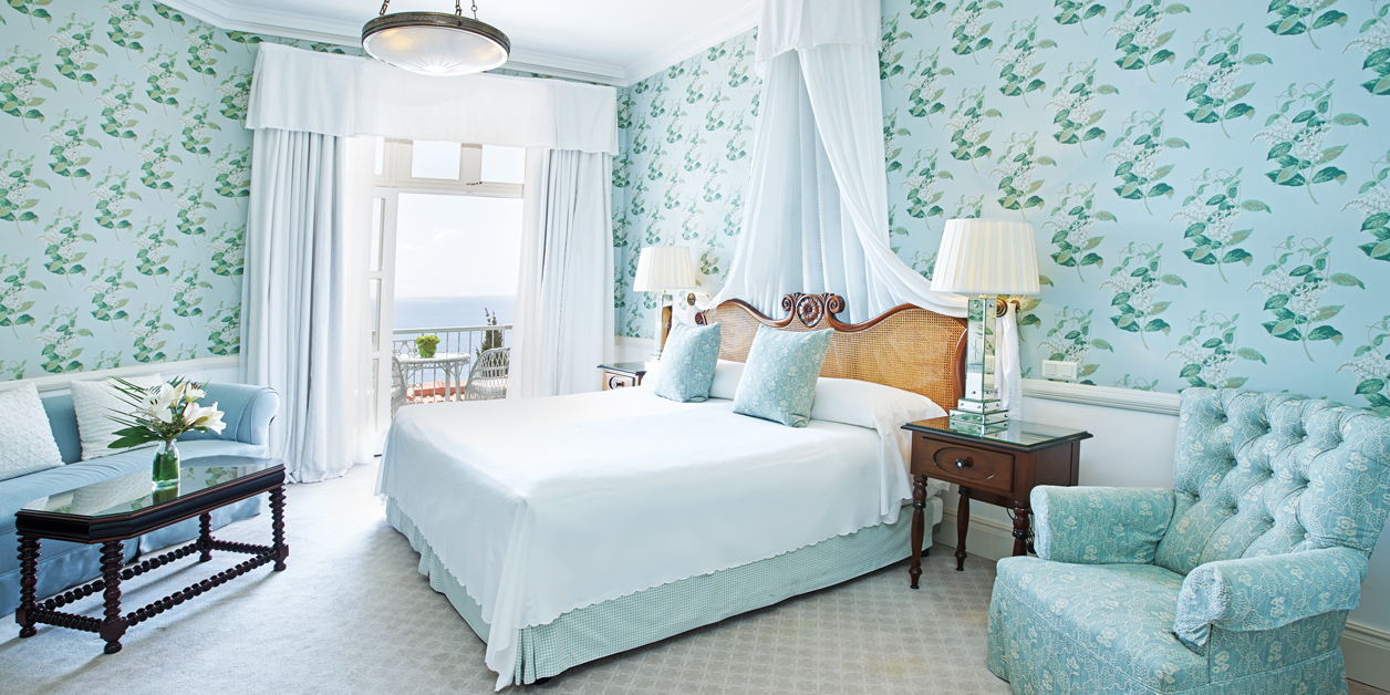 View of junior suite at Belmond Reid's Palace with floral print walls all in tourquise
