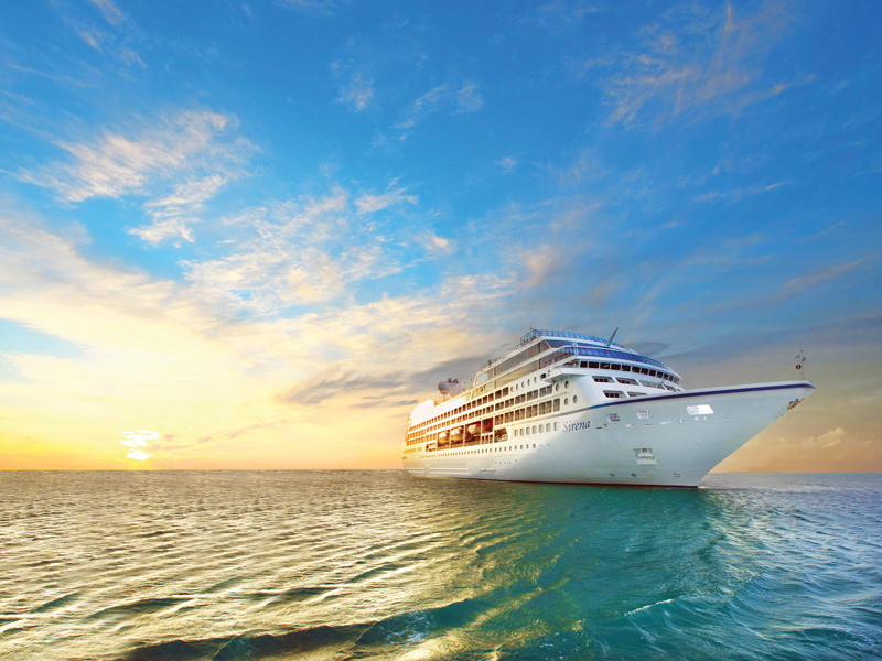 Oceania Sirena ship out to sea with sun setting and vibrant colored sky and ocean