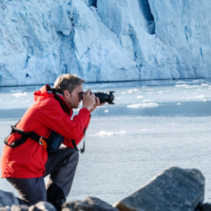 Silversea Guests during an excursion taking photos with glaciers in background in the Arctic