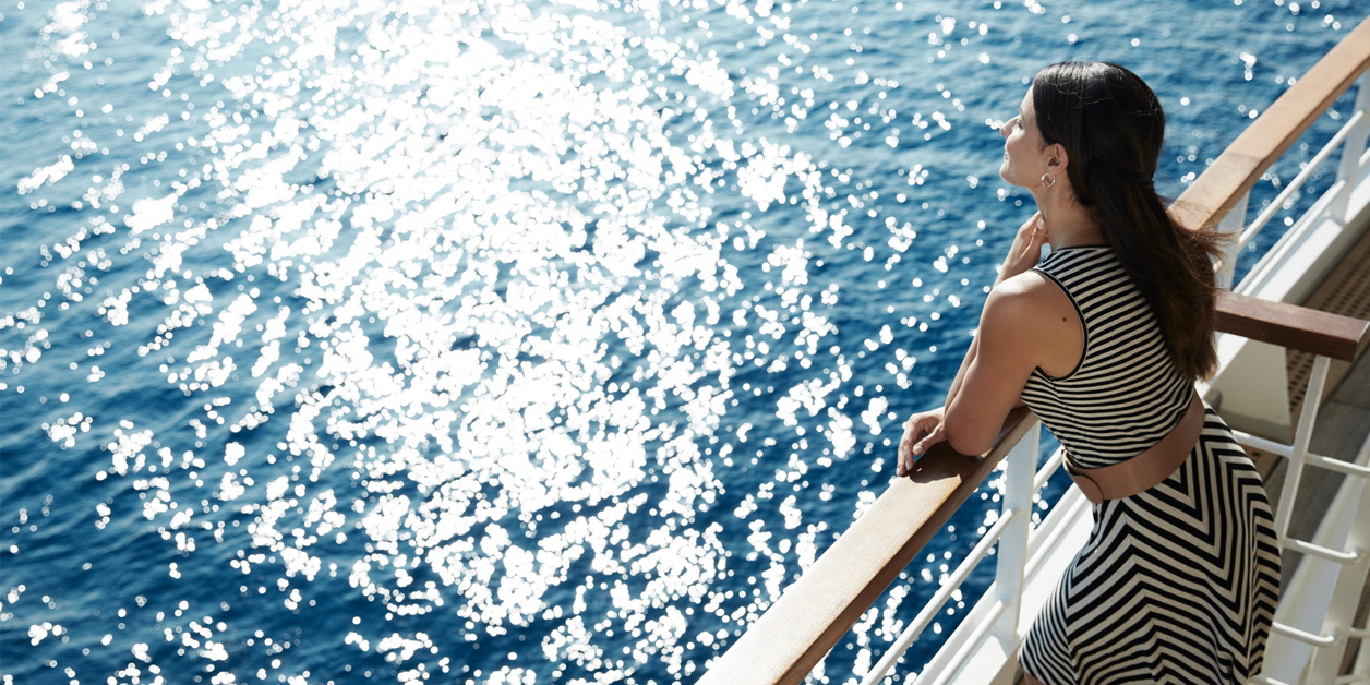 Woman leaning on the railing of a Seabourn ship, looking at the ocean water.