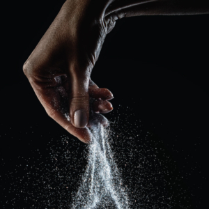 Hand dropping salt with black background, promoting Silversea bar.