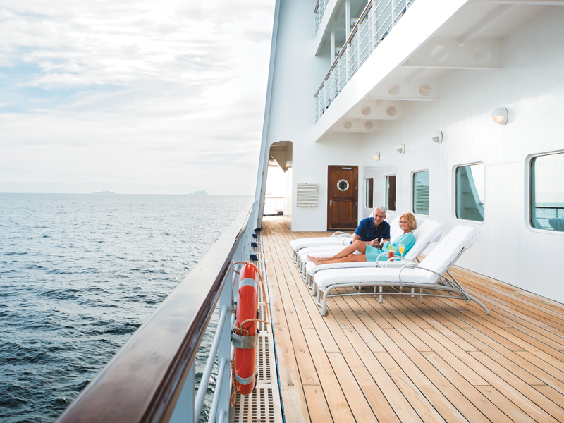 A couple sitting on lounge chairs alone on the deck of a Regent Seven Seas Ship