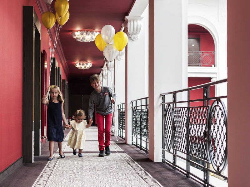 Le Régina Biarritz Hôtel & Spa - MGallery photo of 3 kids with balloons walking by railing.