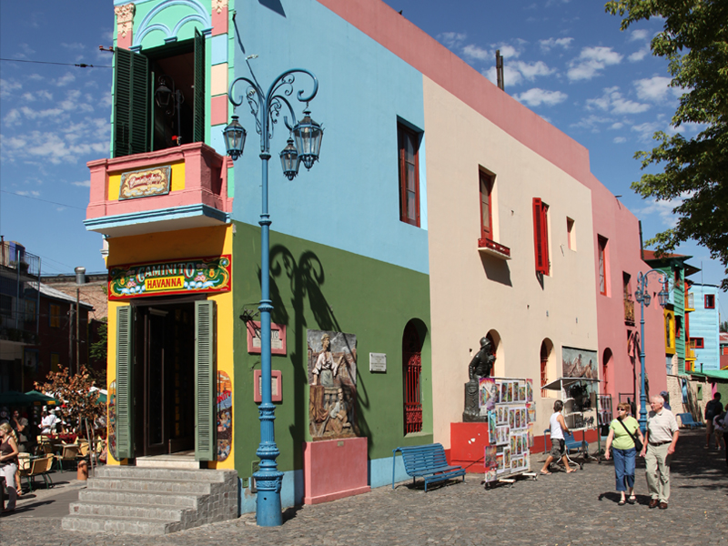 Colorful building on a street in Buenos Aires, with people passing by.