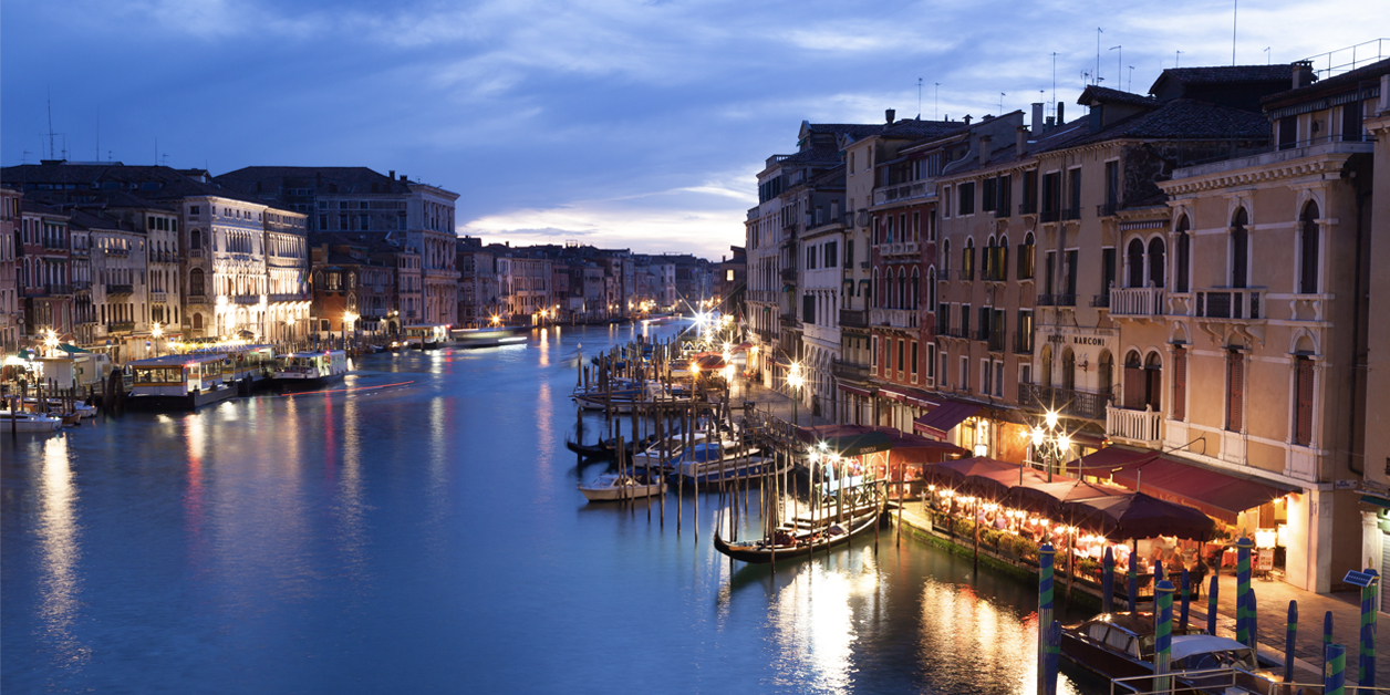 Night view of Grand Canal from Rialto bridge with gondolas in Venice, Italy.