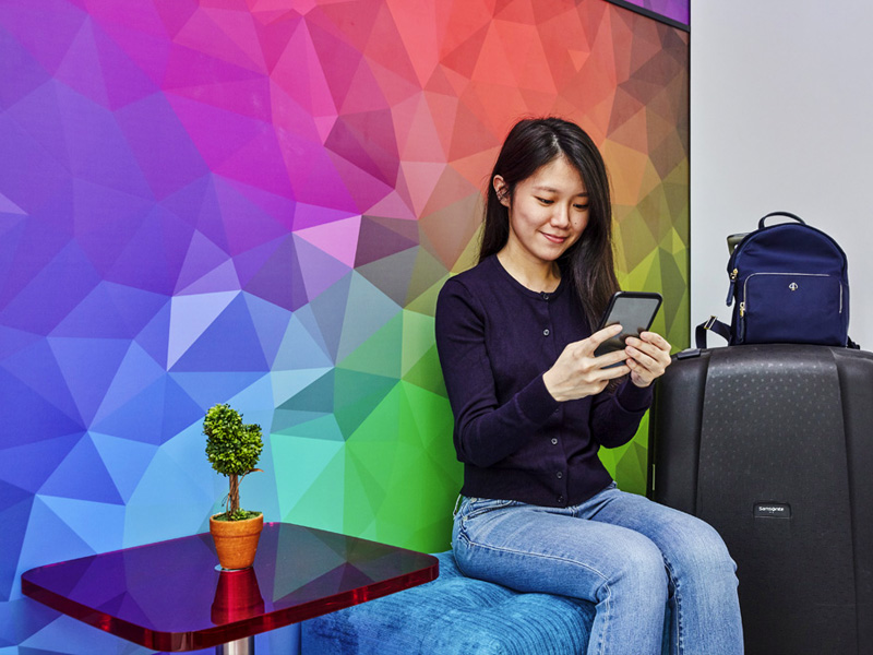 Woman sitting with luggage, looking at phone in front of colorful wall at ibis budget Singapore Ametrine