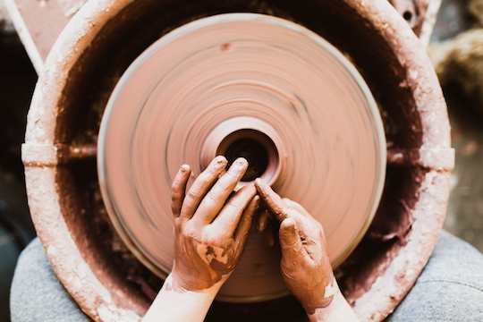 Image of hands shaping a pot on a pottery wheel