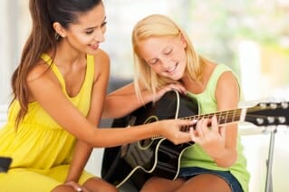 Teenagers take guitar lessons
