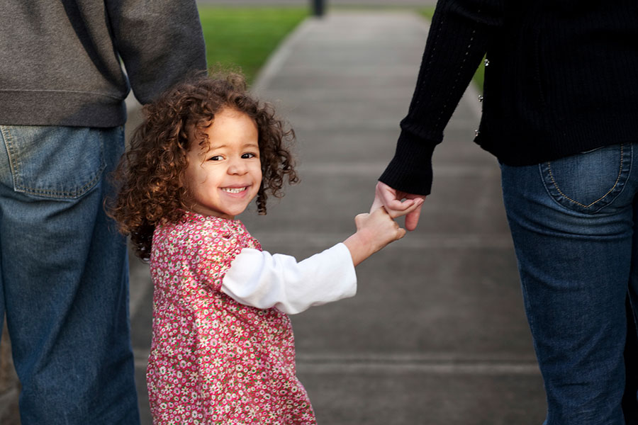 Girl holding hands with mom and dad
