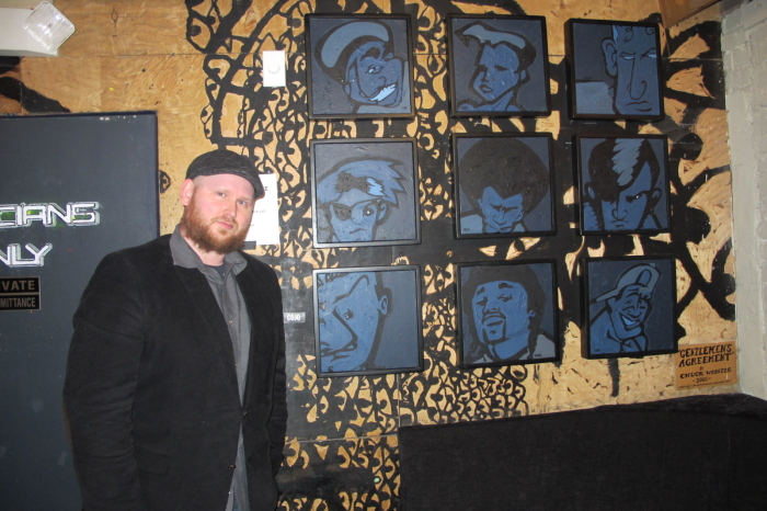 Artist Cojo next to his work