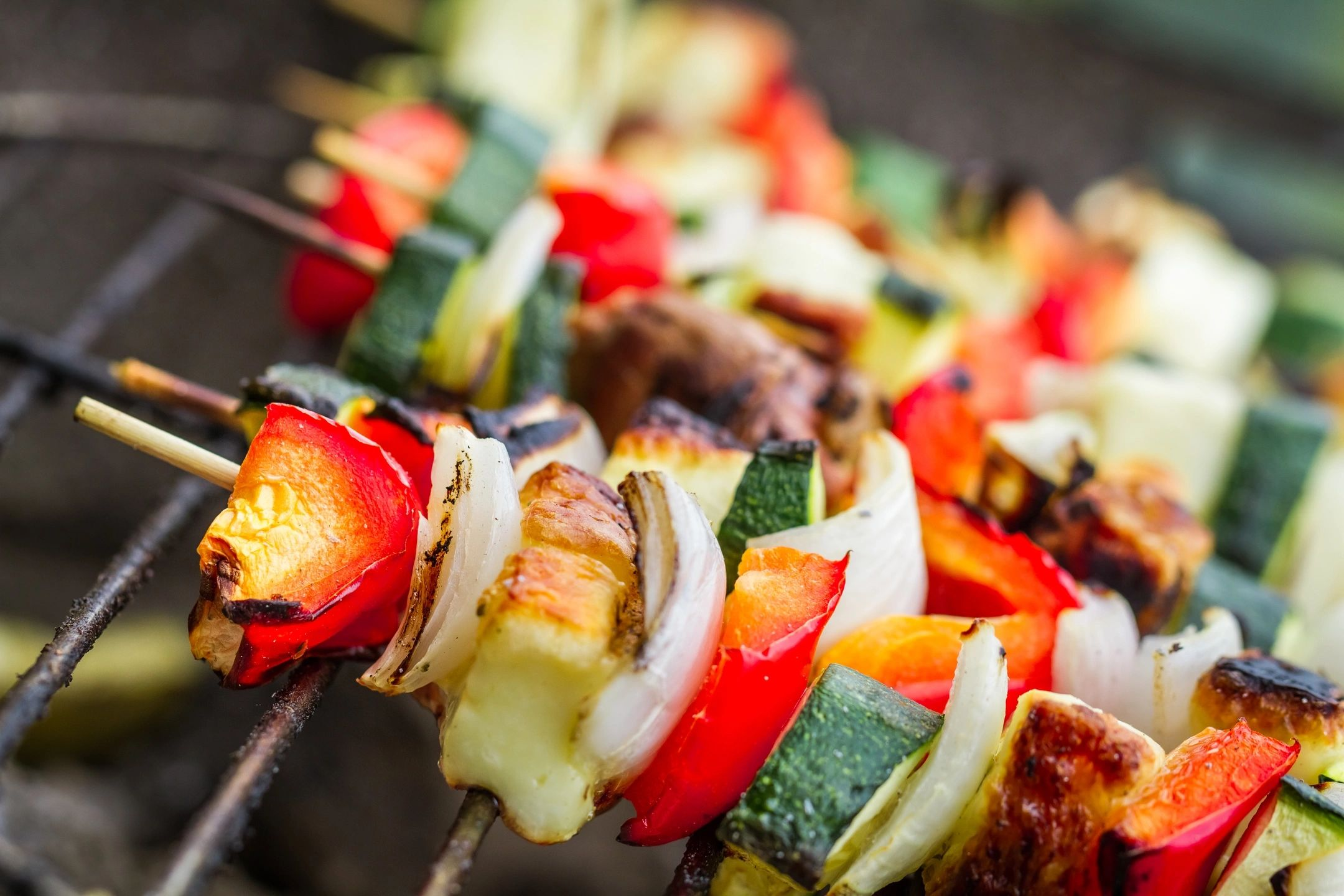 Photo of several vegetable kebabs on a grill
